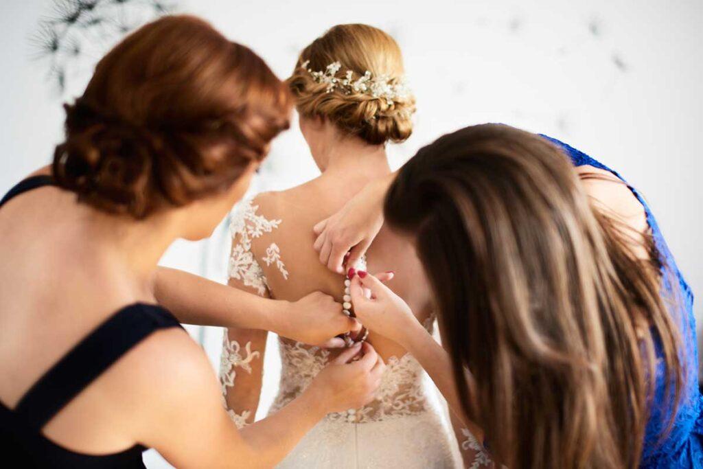 druhny zapinają guziki na sukni ślubnej
