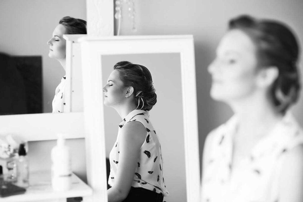 panna młoda poczas makijażu ślubnego przy lustrach
