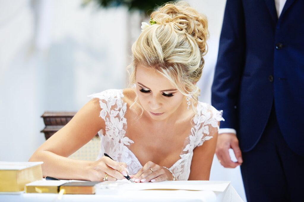 panna młoda podpisująca dokumenty ślubne
