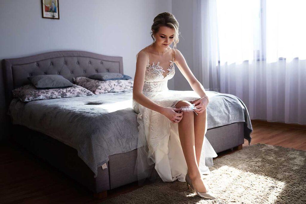 panna młoda zakłada ślubną podwiązkę