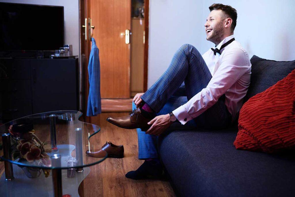 uśmiechnięty pan młody zakłada buty do ślubu