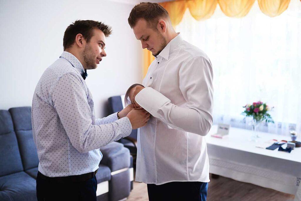pan młody z bratem ubiera koszulę