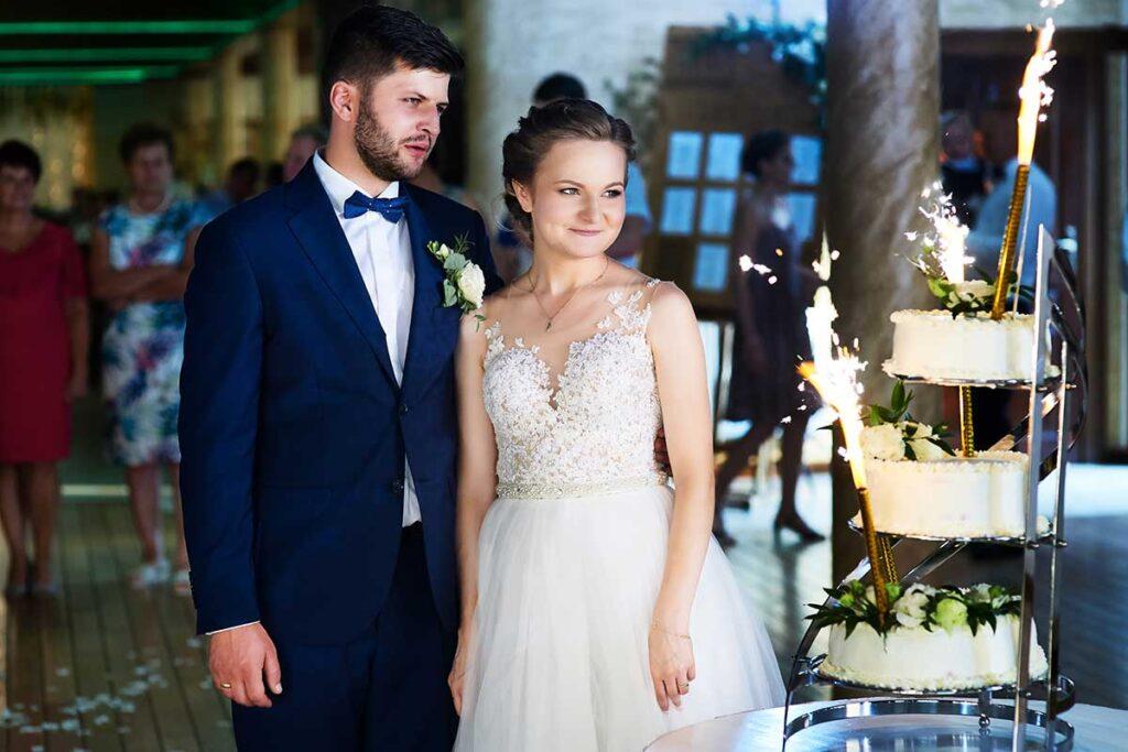 para młoda w trakcie krojenia torta weselnego